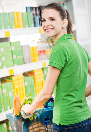 everyday people: Smiling woman in green polo shirt shopping at store rear view.