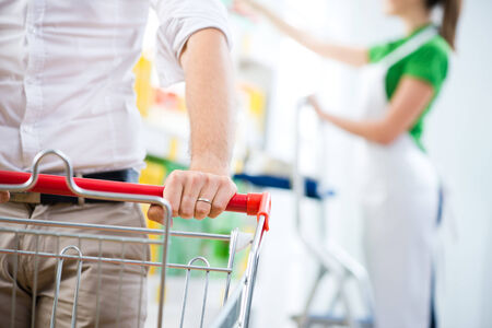 sales clerk: Supermarket customers hand close-up with sales clerk on background. Stock Photo