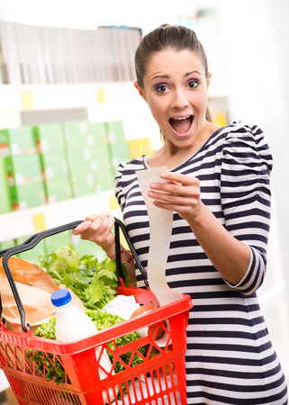 Astonished young woman with full shopping basket checking a grocery receipt.