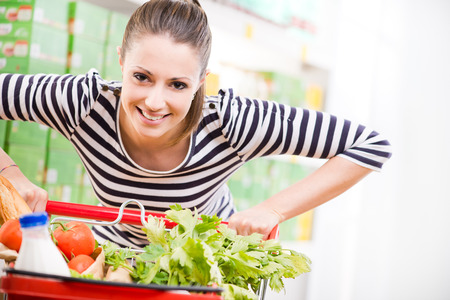 grocery shopping cart: Attractive young woman smiling and pushing a cart at supermarket.