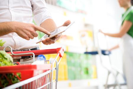 store clerk: Customer using a digital tablet at supermarket with sales clerk on background.