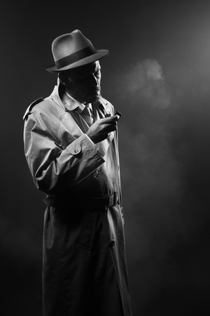 Handsome man in trench coat lighting a cigarette in the dark