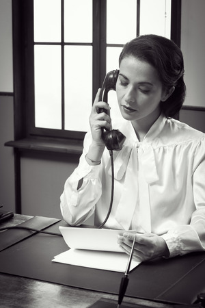 retro phone: Attractive vintage secretary working at desk and having a phone call