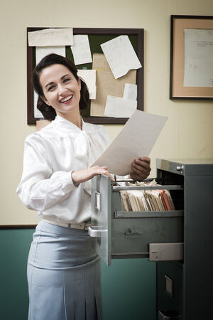 filing cabinet: Smiling vintage secretary searching files in the filing cabinet open drawers Stock Photo