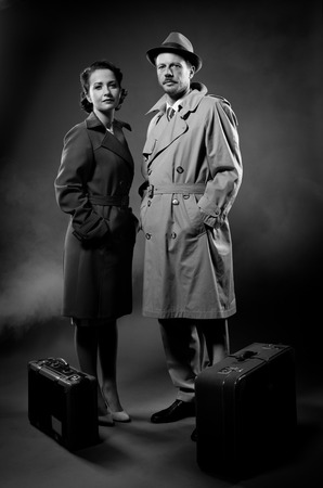 Film noir: elegant couple ready to leave with luggage waiting with hands in pockets Stock Photo