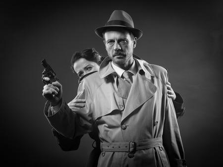 thriller: Thriller film noir scene with man pointing a gun and woman hiding behind him