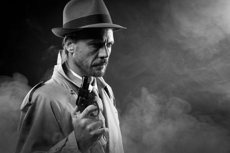 Handsome Detektiv in Trenchcoat hält eine Waffe in der Dunkelheit, Film Noir