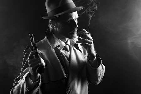 thriller: Film noir: attractive gangster in trench coat smoking a cigarette and holding a revolver