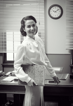 to the secretary: Cute vintage secretary working at office, smiling and holding a folder with paperwork Stock Photo