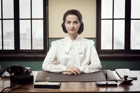 desk clerk: Attractive vintage business woman sitting at office desk and smiling at camera