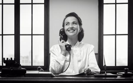 secretaria: Recepcionista sonriente vendimia trabaja en el escritorio de oficina y sonriente