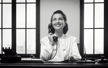telephone receiver: Smiling vintage receptionist working at office desk and smiling