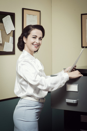 filing cabinet: Smiling vintage secretary searching files in the filing cabinet drawers