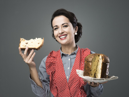 old people eating: Vintage woman in apron eating a slice of panettone, traditional italian homemade pastry