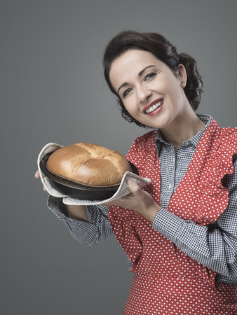 home made: Smiling vintage woman holding an homemade cake in a baking tin Stock Photo