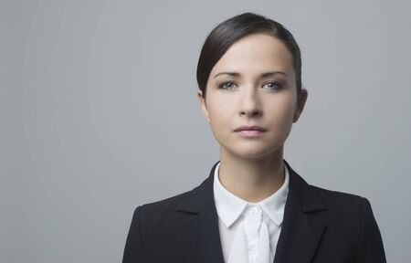 Serious confident businesswoman staring at camera and posing on gray background.