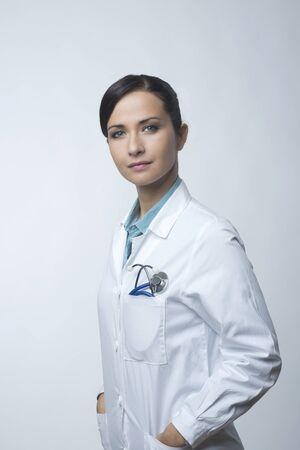 bata de laboratorio: Confiado doctora sonriente posando con bata de laboratorio y un estetoscopio. Foto de archivo