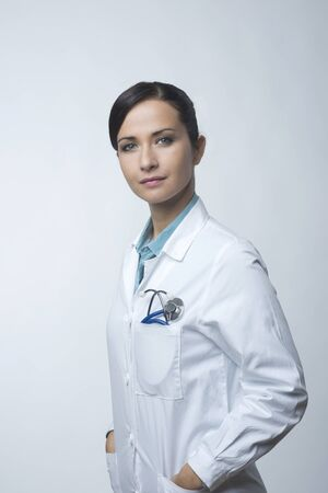 Confident smiling female doctor posing with lab coat and stethoscope. Stock Photo