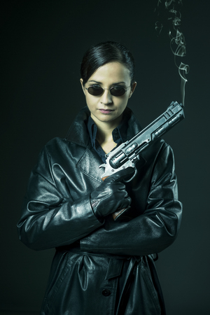 Attractive female agent in black leather coat and sunglasses holding a gun.