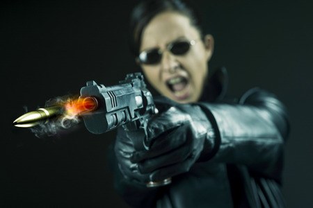 Female agent in leather coat and sunglasses pointing a gun and shouting. Imagens