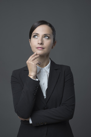 chin: Attractive pensive business woman with hand on chin looking away.