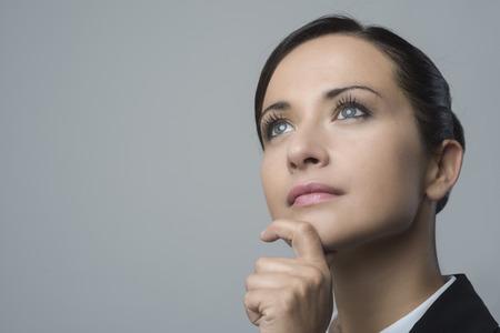 mujer pensativa: Atractiva mujer de negocios pensativa con la mano en la barbilla mirando a otro lado.