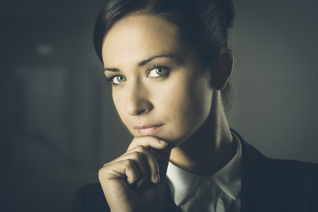 elegant woman: Joven empresaria atractiva sobre fondo oscuro pensando con la mano en la barbilla.