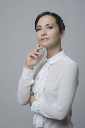 jabot: Attractive woman in white elegant shirt with hand on chin, smiling at camera.