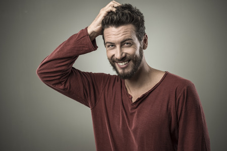 hombres jovenes: Dudoso hombre sonriente joven que toca la cabeza y pensando
