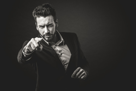 aggressive people: Aggressive businessman pointing finger against dark background