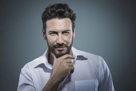beau jeune homme: Homme souriant Handsome avec la main sur le menton pose