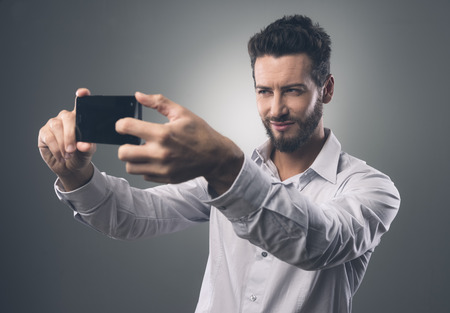 Cool handsome man taking self portraits with his smartphone photo