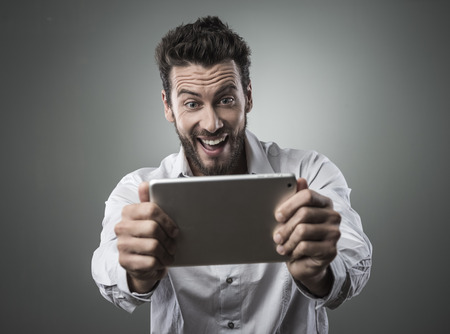 Cheerful smiling man watching videos and playing video games on his tablet