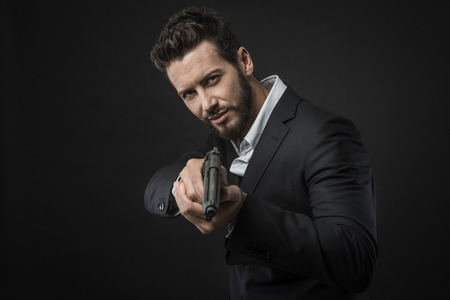 Cool aggressive man in shirt and jacket pointing a gun Stock Photo