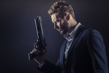 man profile: Brave cool man holding a dangerous weapon on dark background