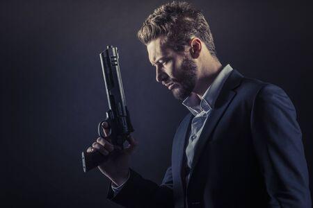 pistolas: Hombre fresco Brave sosteniendo un arma peligrosa en fondo oscuro Foto de archivo