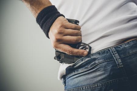 undershirt: Man grabbing quickly a pistol, hands close up