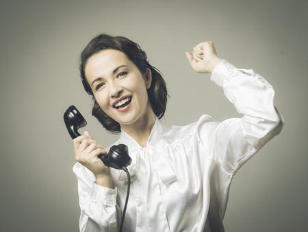 good news: Cheerful vintage secretary receiving good news on the phone with fist raised
