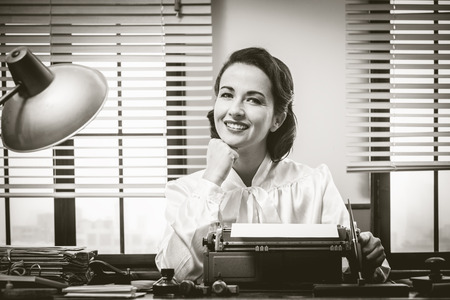 1950s style secretary working at office desk and smiling with hand on chin