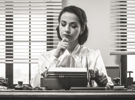 Peinzende vintage vrouw met de hand op de kin, het typen op de typemachine en op zoek naar inspiratie
