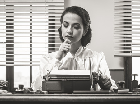 Pensive vintage woman with hand on chin, typing on typewriter and looking for inspiration Archivio Fotografico