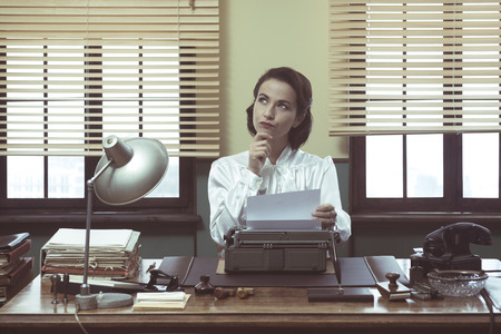 Pensive vintage woman with hand on chin, typing on typewriter and looking for inspiration 스톡 콘텐츠