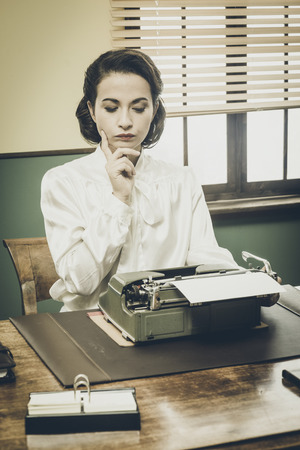 creative writer: Pensive vintage woman with hand on chin, typing on typewriter and looking for inspiration Stock Photo