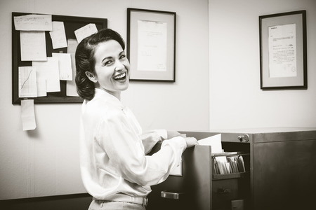 file clerks: Smiling vintage secretary searching files in the filing cabinet open drawers Stock Photo