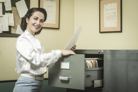 Smiling vintage secretary searching files in the filing cabinet drawers