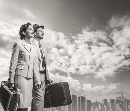 Elegant vintage couple walking and holding suitcases, skyline on background photo