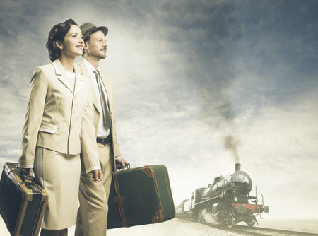 Elegant vintage couple walking and holding suitcases with steam train on background, travel concept