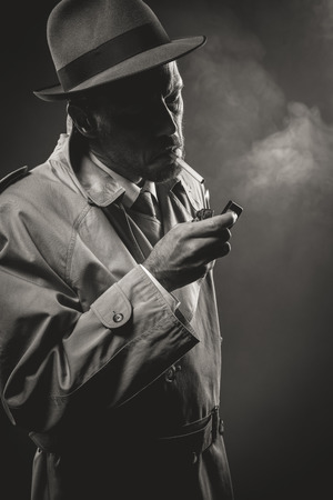 trench coat: Handsome man in trench coat lighting a cigarette in the dark