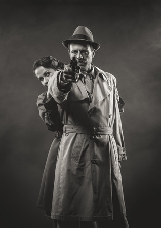 fedora hat: Thriller film noir scene with man pointing a gun and woman hiding behind him