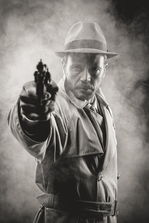 mystery man: Vintage agent pointing a gun in the dark, film noir scene 1950s style Stock Photo